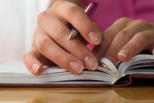 Nice hands with french manicure on the notebook.
