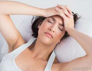 woman-in-white-lying-against-white-sheets-with-headache