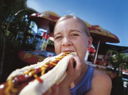 Girl eating a hotdog.
