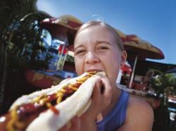 Girl eating a hotdog.
