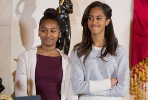 epa04505139 Daughters of US President Barack Obama (not pictured) Sasha (L) and Malia (R) listen to their father deliver remarks during the pardoning of the National Thanksgiving Turkey ceremony in the Grand Foyer of the White House in Washington DC, USA, 26 November 2014. This year's turkey, 'Cheese' and alternate 'Mac', both about 48 pounds (21.7 kilograms), were raised in Ohio and will travel to their permanent home at Morven Park's 'Turkey Hill' - a historic turkey farm in Leesburg, Virginia. EPA/MICHAEL REYNOLDS ORG XMIT: MHR01