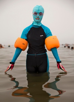 QINGDAO, CHINA - AUGUST 21: A Chinese woman wears a face-kini as she poses on August 21, 2014 in the Yellow Sea in Qingdao, China. The locally designed mask is worn by many local women to protect them from jellyfish stings, algae and the sun's ultraviolet rays. (Photo by Kevin Frayer/Getty Images)